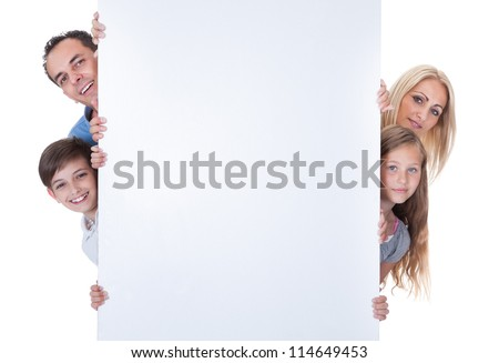 Portrait Of Family With Two Children Peeping Behind Blank Board On White Background