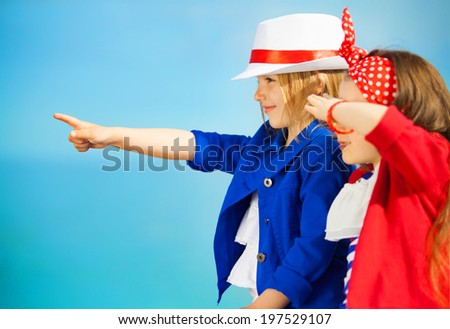 Portrait of fashion kids points to the sea. Vacation, friendship, fashionable concept