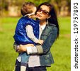 Portrait of fashionable baby boy and his gorgeous mother (hollywood star) in trendy sunglasses walking in the street. Kid kissing mom. Sunny spring day. Outdoor shot - stock photo
