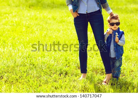 Portrait of fashionable baby boy in trendy sunglasses and his mother standing in the park. Son shows thumb up (ok sign). Sunny spring day. Hipster style. Copy-space. Outdoor shot