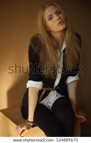 Portrait of fashionable model with long red hair in black jacket, white shirt, posing over wooden background. Natural style. Daylight. Studio shot