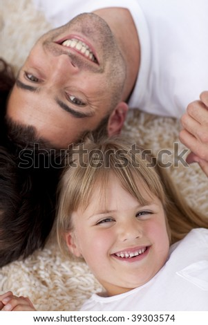 Portrait of father and daughter on floor lying with heads together