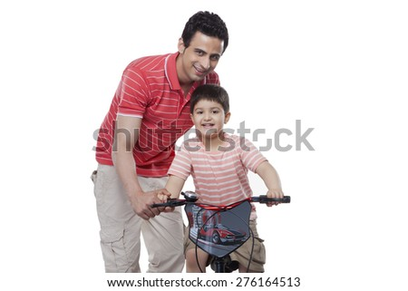 Portrait of father teaching son to ride bicycle against white background
