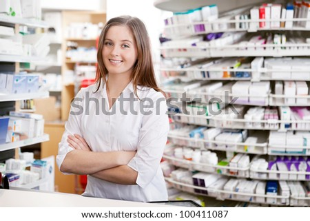 Portrait of female pharmacist standing with arms crossed at counter in pharmacy