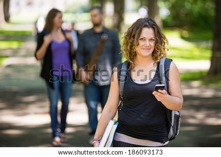 Portrait of female student with backpack holding cellphone while standing on campus