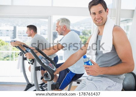 Portrait of fit man on exercise bike holding water bottle at gym