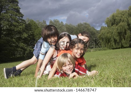 Portrait of five children lying on top of each other in meadow