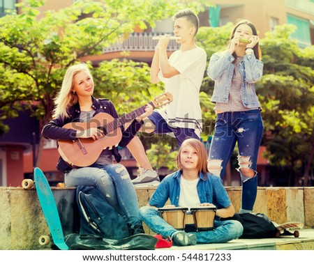 Portrait of four cheerful smiling teenagers playing music together outdoors