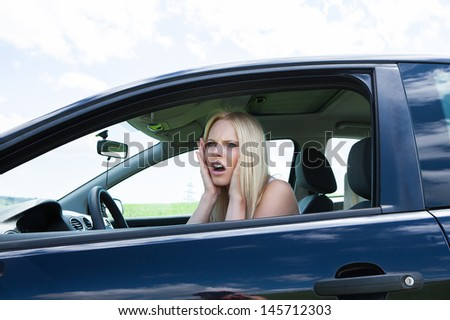 Portrait Of Frustrated Woman Screaming Sitting In Car