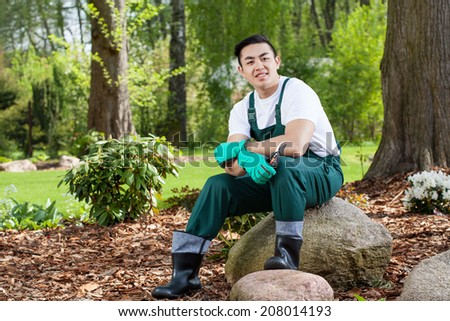 Portrait of gardener sitting on a rock in garden