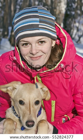 Portrait of girl with dog in winter Park closeup.