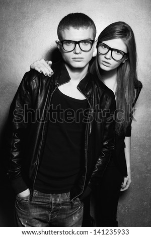 Portrait of gorgeous blond fashion twins in black clothes wearing trendy glasses & posing over silver metal  background together. Perfect hair. Natural make-up. Perfect skin. Black & white studio shot