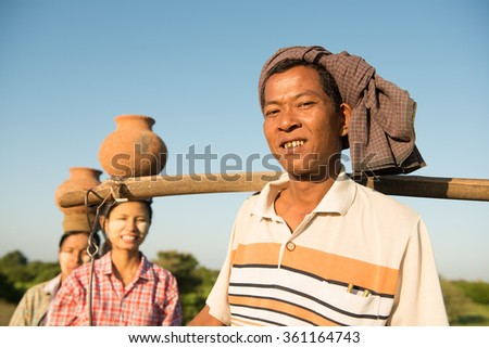 Portrait of group Asian Burmese traditional farmers carrying clay pots on head, Bagan, Myanmar