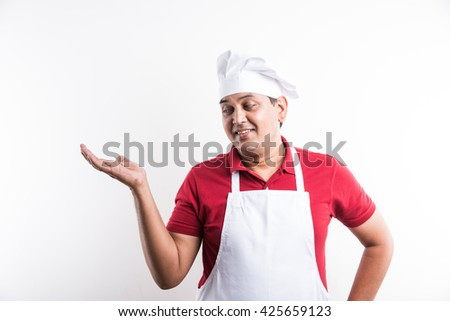 portrait of handsome indian male chef introducing something , asian male chef presenting something, isolated over white background