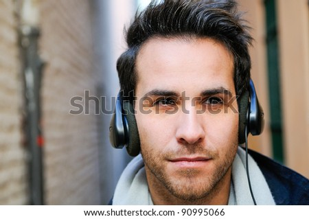 Portrait of handsome man in urban background listening to the music with headphones