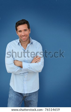 Portrait of handsome man standing on blue background