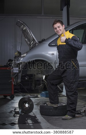 Portrait of handsome mechanic based on car in auto repair shop smiling