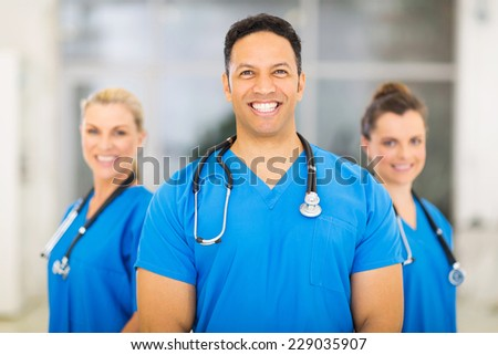 portrait of handsome medical doctor with colleagues on background