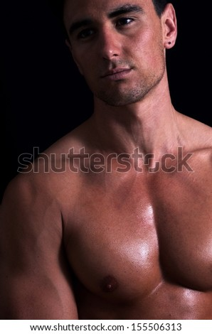 portrait of handsome nude man over dark background