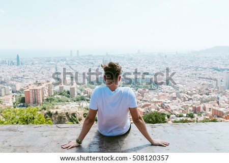 Portrait of handsome young man looking at the views form the top of a mountain.