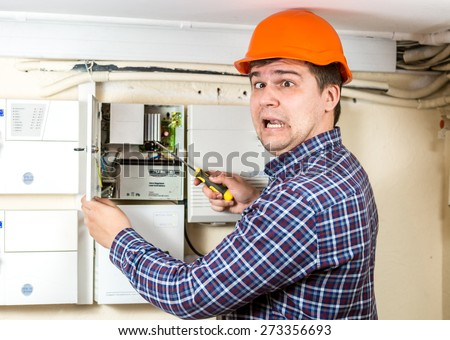 Portrait of handyman being hit by high voltage while repairing transformer at home