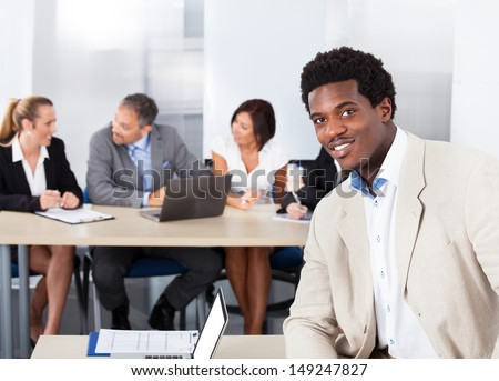 Portrait Of Happy African Businessman Sitting In Front Of Colleagues