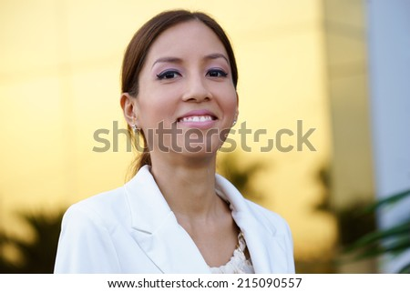 Portrait of happy and self confident latina businesswoman in tailleur smiling at camera in office