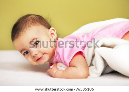 Portrait of happy Baby lying on white towel
