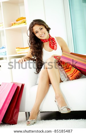 Portrait of happy brunette looking at camera while sitting on sofa after shopping