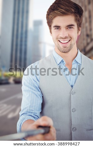 Portrait of happy businessman holding selfie stick against new york street