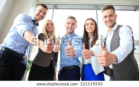 Portrait of happy businesspeople standing in office showing thumb up
