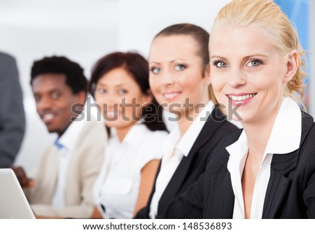 Portrait Of Happy Businesswoman Sitting With Her Colleagues