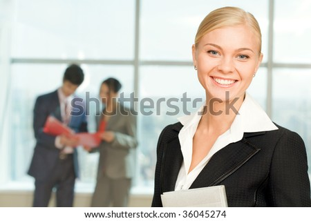 Portrait of happy businesswoman smiling at camera on background of working people