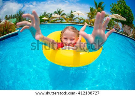 Portrait of happy child with inflatable rubber circle having fun in swimming pool