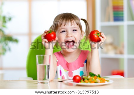 Portrait of happy child with vegetables sitting at table