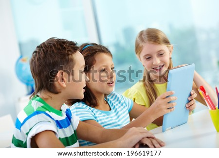 Portrait of happy classmates at workplace using digital tablet