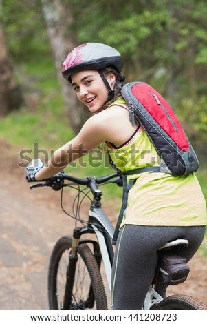 Portrait of happy confident biker on footpath