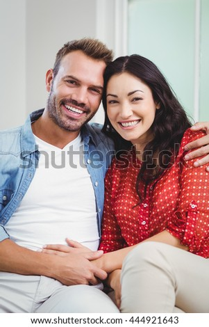 Portrait of happy couple sitting on sofa in living room