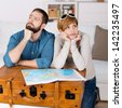 Portrait of happy couple with map leaning on suitcase in house - stock photo