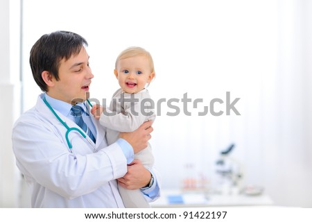 Portrait of happy cute baby on hands of pediatrician