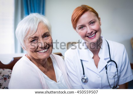 Portrait of happy doctor and patient at home