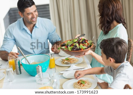 Portrait of happy family of three sitting at dining table in the home