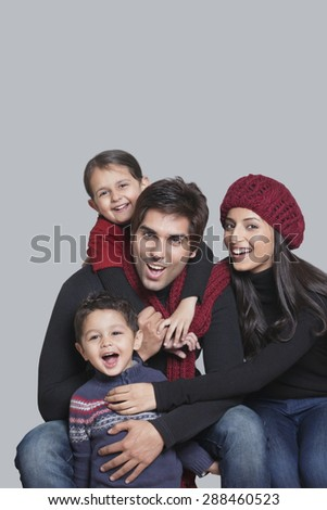 Portrait of happy family over grey background