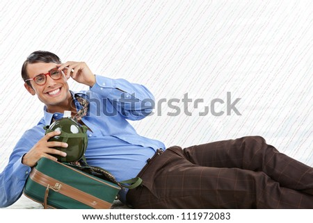 Portrait of happy geek businessman lying down with travel bag on textured background