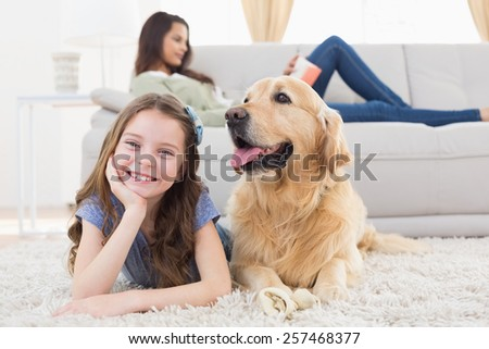Portrait of happy girl with dog on rug while mother relaxing at home