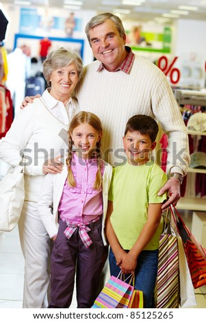 Portrait of happy grandparents and grandchildren during shopping
