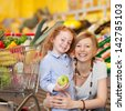 Portrait of happy little girl holding apple while mother embracing her in grocery store - stock photo