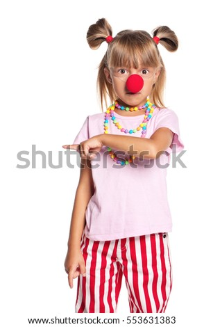 Portrait of happy little girl with red clown nose, isolated on white background. Child pointing at copy space.
