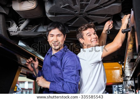 Portrait of happy male mechanics working under lifted car at auto repair shop