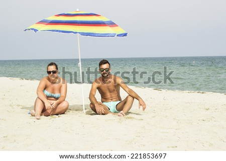 Portrait of happy man and women siting on sand under umbrella